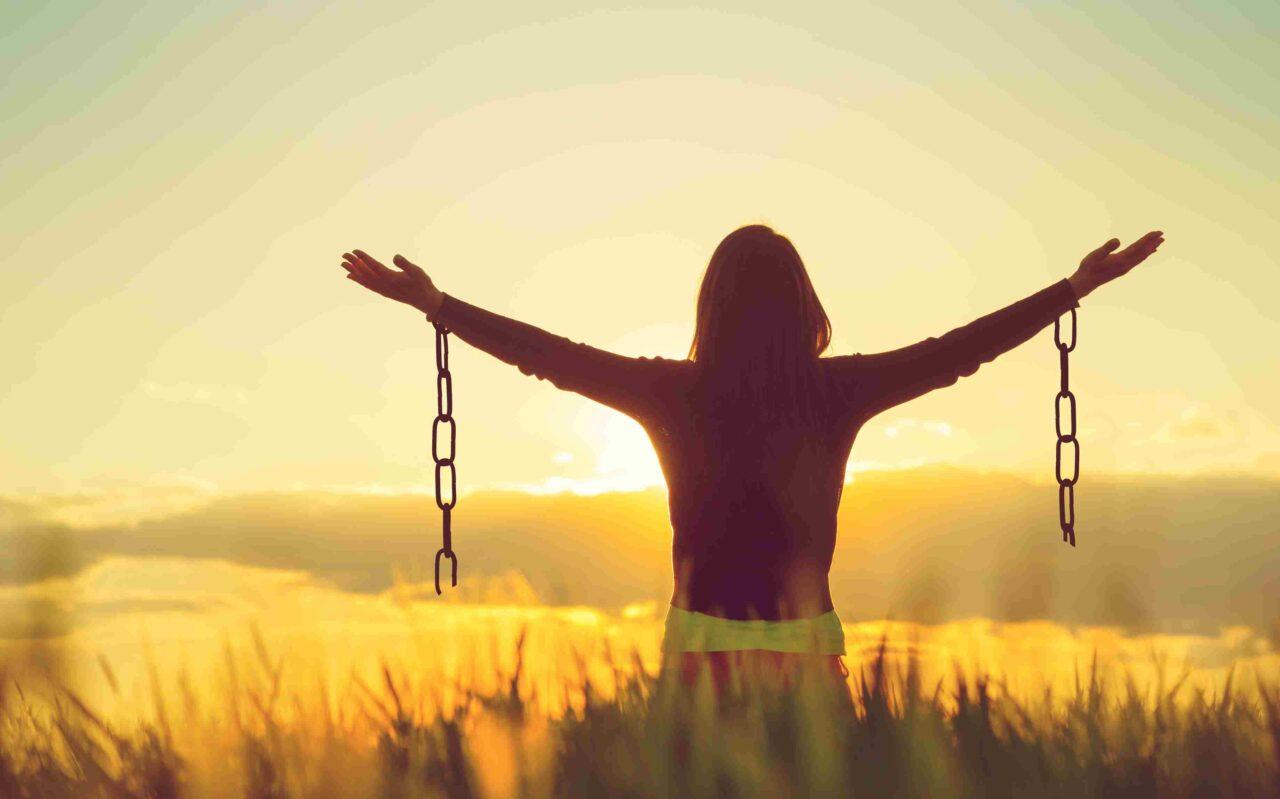 Eine Frau mit ausgestreckten Armen vor einem Sonnenuntergang. An beiden Handgelenken hängen Reste einer gesprengten Kette.